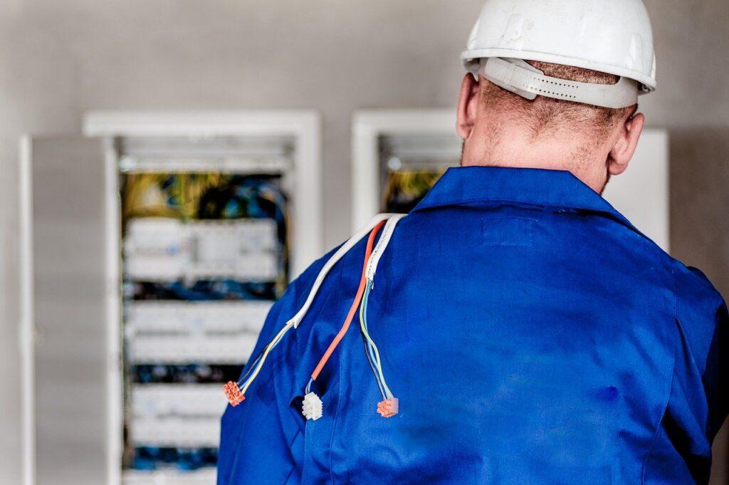 Person med ledninger over skulderen, på vej imod en el tavle