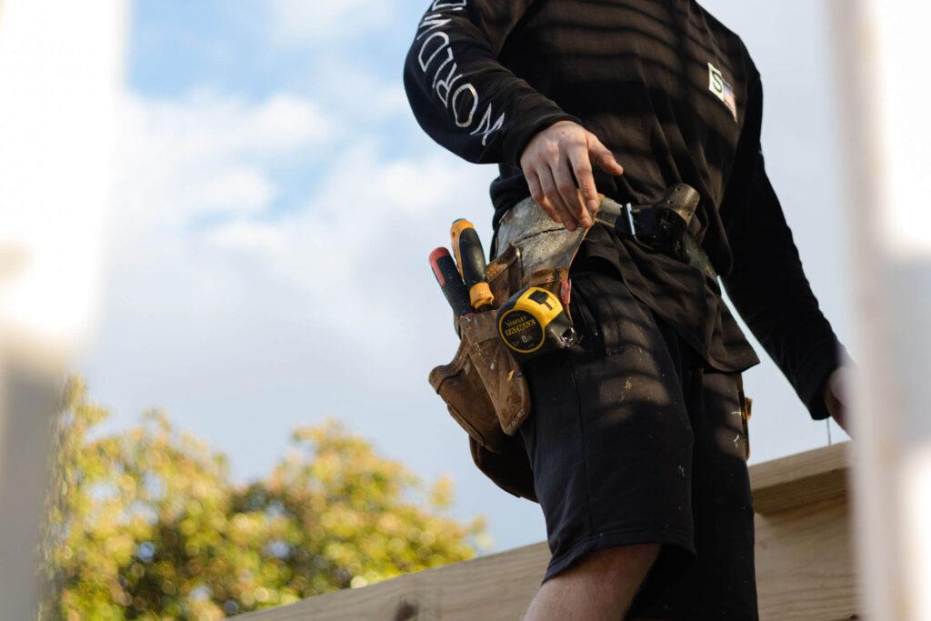 Person med arbejdsbælte, der giver lommer. Har værktøj i lommerne.